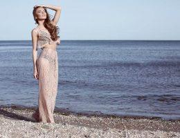 Bohem Elbise giyen ve Bohem Giyim Tarzına Sahip olan kadın Bozcaada sahilinde gün batımında yüzünü güneşe dönmüş otantik takıları ile poz vermekte